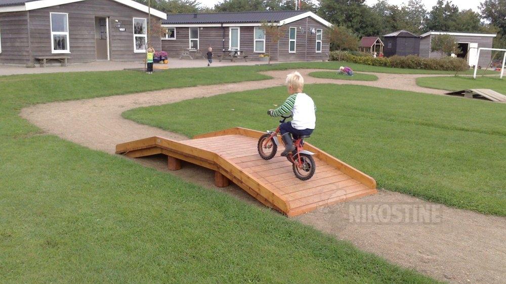 Lille dreng kører med cykel over bro